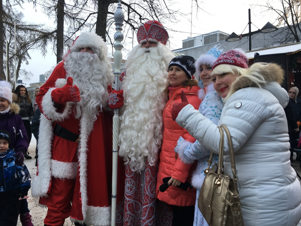 Finland's Santa, left, and Russia's Grandfather Frost, 2nd left, meet families in the border town of Lappeenranta, Finland on Monday De...