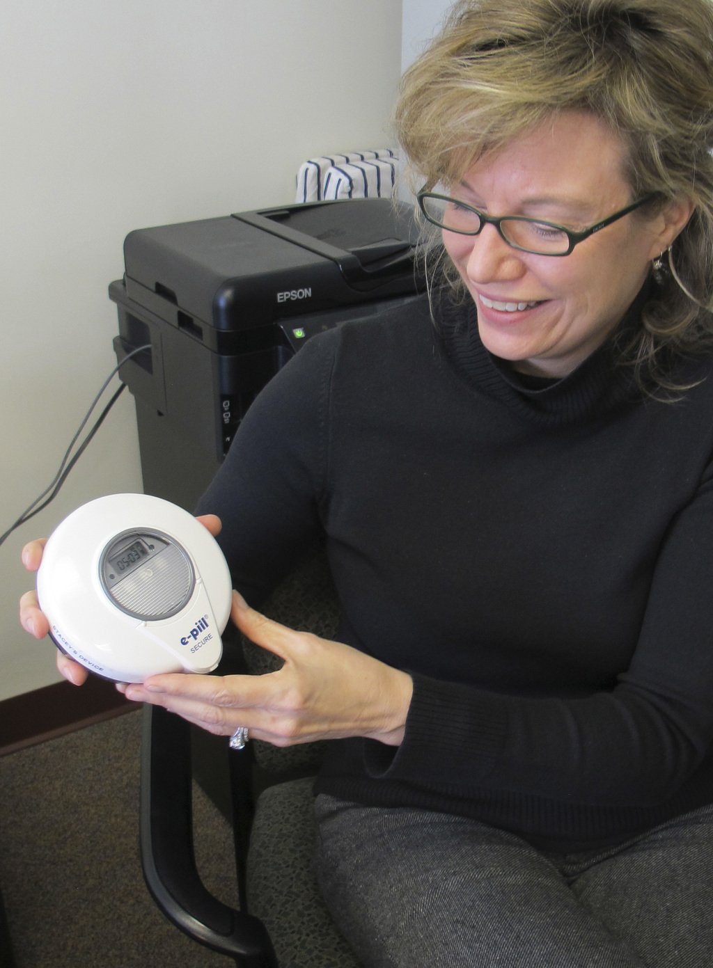 University of Vermont Psychologist Stacey Sigmon holds a tamper-proof electronic pill dispenser in her office in Burlington, Vt., Wedne...