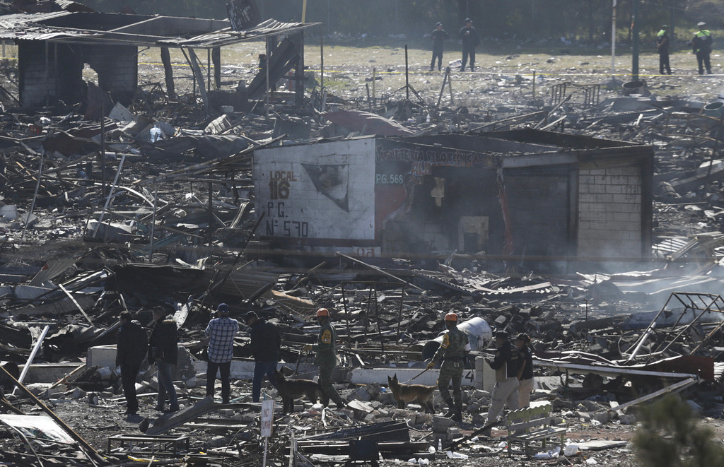 Soldiers and investigators walk through the scorched rubble of the open-air San Pablito fireworks market in Tultepec on the outskirts o...