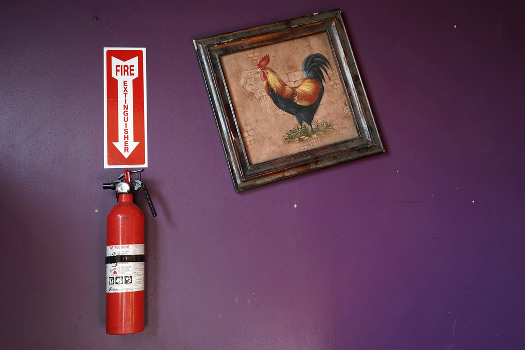 This Dec. 19, 2016 photo shows a fire extinguisher hanging on the wall at an underground music club known as known as Purple 33 in a Pl...