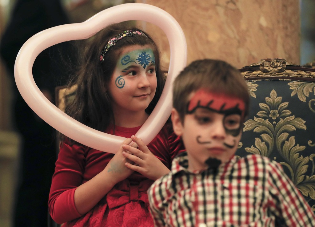 In this Tuesday, Dec. 13, 2016 photo, a girl holds a heart shaped balloon during a Christmas show for children of Romanian military fam...