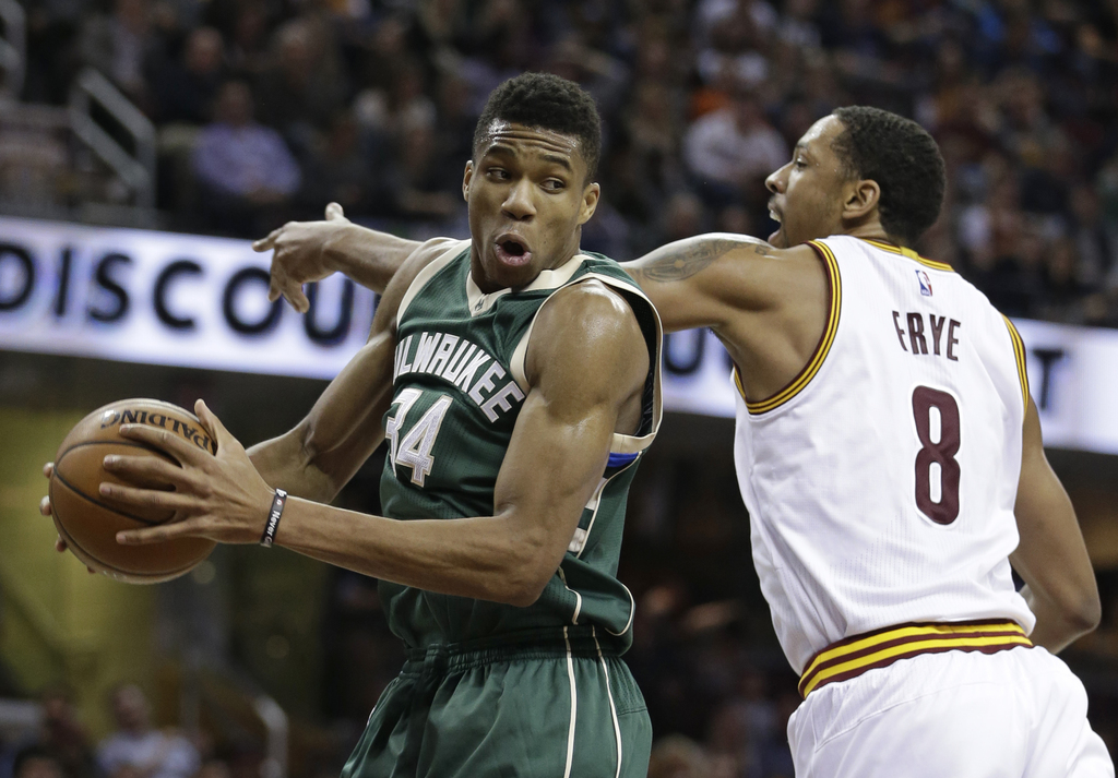 Milwaukee Bucks' Giannis Antetokounmpo (34) grabs a rebound ahead of Cleveland Cavaliers' Channing Frye (8) during the first half of an...