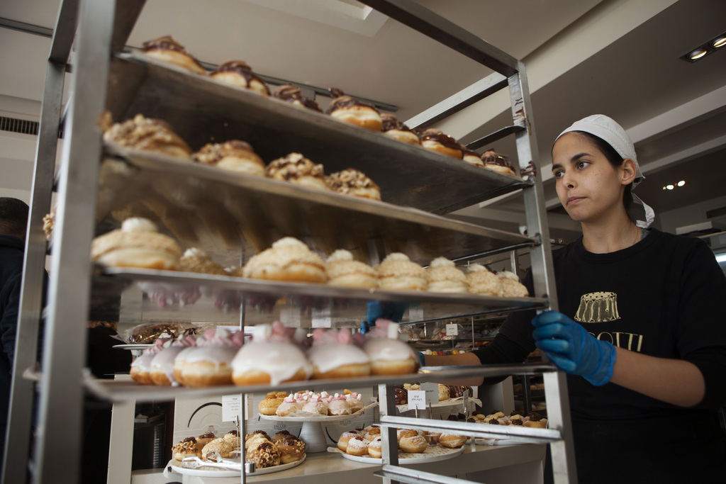 In this Thursday, Dec. 15, 2016 photo, a bakery employee wheels doughnuts in Bnei Brak, Israel. Israelis are finding new advice hard to...