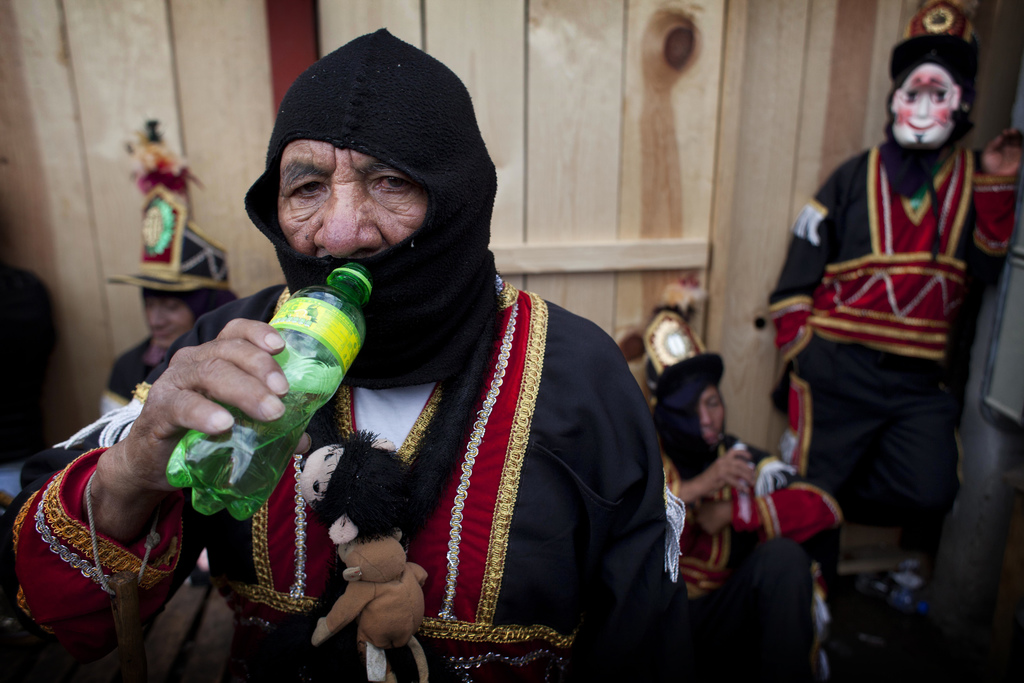 A dancer drinks water as he rests during celebrations honoring Saint Thomas, the patron saint of Chichicastenango, Guatemala, Wednesday...