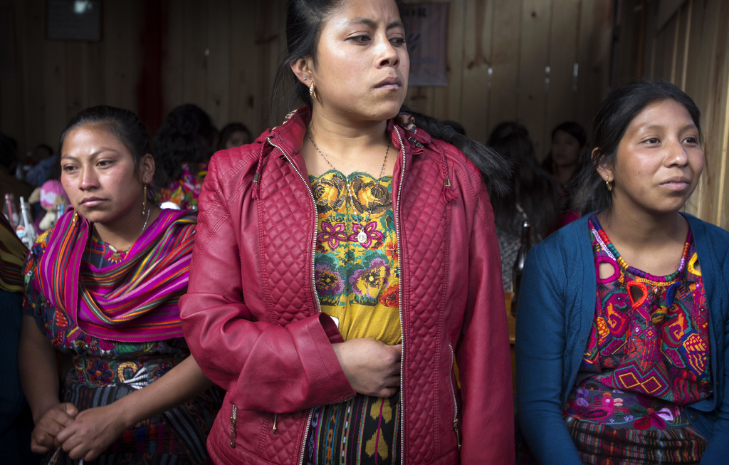 Indigenous women watch fireworks being launched during celebrations honoring Saint Thomas, the saint patron of Chichicastenango, Guatem...