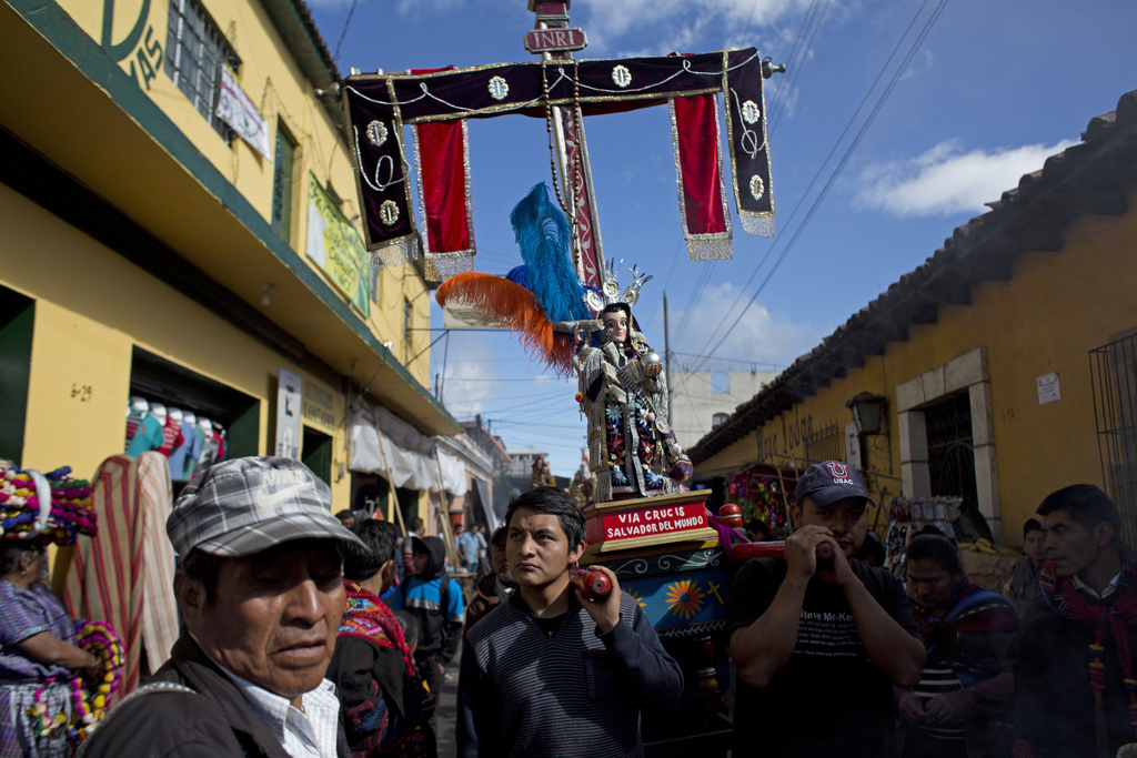 Men carry a religious statue during a procession in honor of Saint Thomas, the patron saint of Chichicastenango, Guatemala, Wednesday, ...