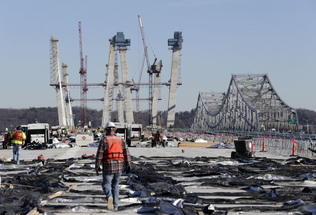 Construction workers walk on the new Tappan Zee Bridge while the old one, right, is still in use near Tarrytown, N.Y., Tuesday, Dec. 20...