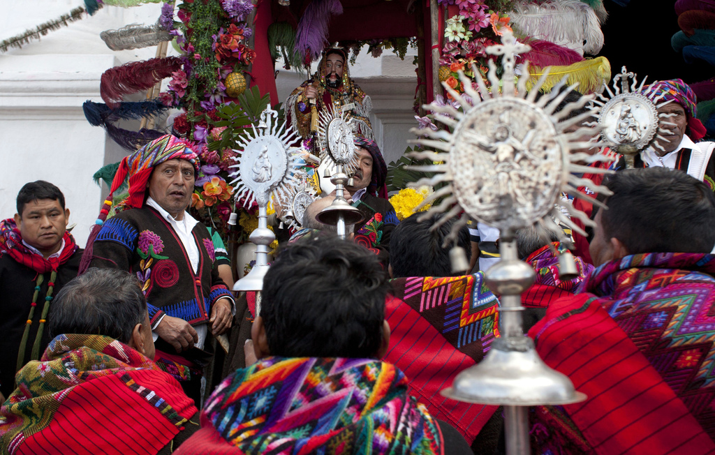 Members of a brotherhood pray after a procession in honor of Saint Thomas, the patron saint of Chichicastenango, Guatemala, Wednesday, ...
