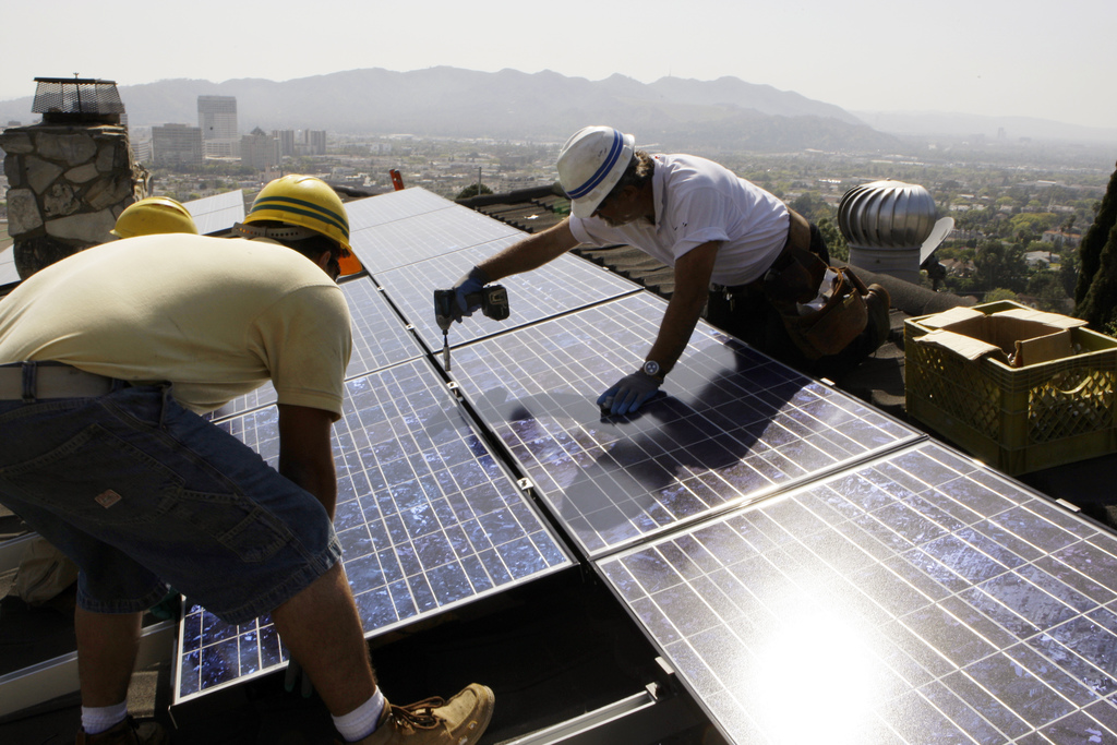FILE - In this March 23, 2010, file photo, installers from California Green Design install solar electrical panels on the roof of a hom...
