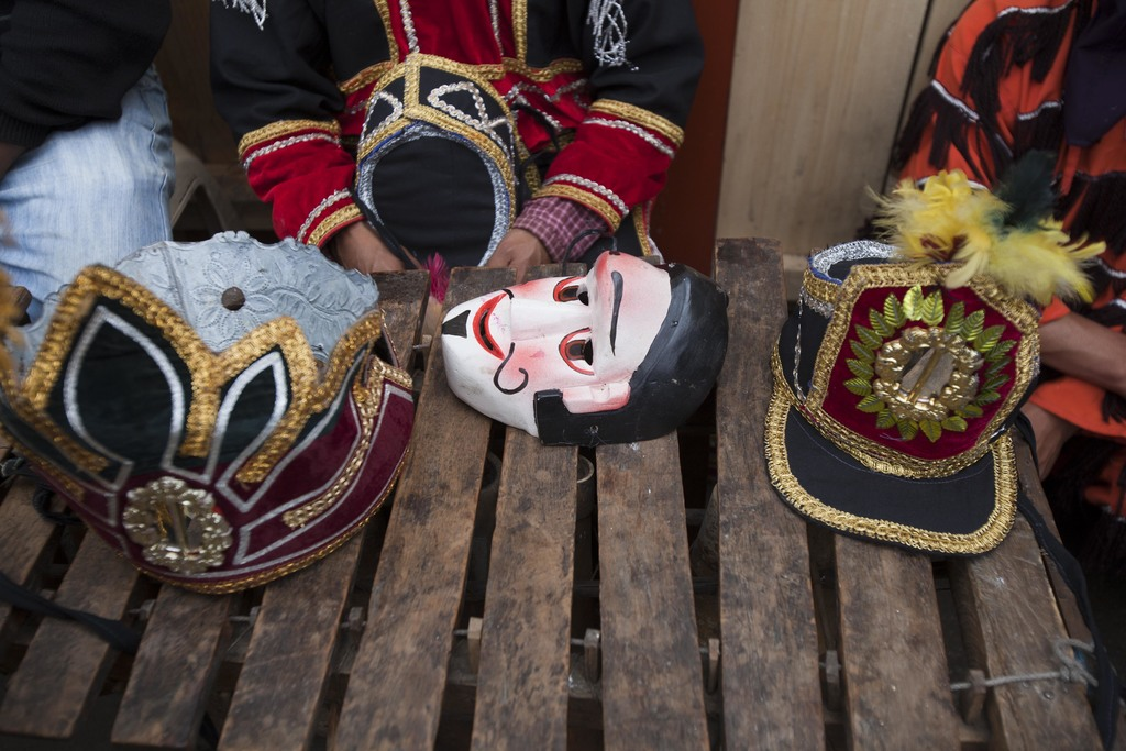 A costume mask and hats sit on a marimba instrument during a break at celebrations honoring Saint Thomas, the patron saint of Chichicas...