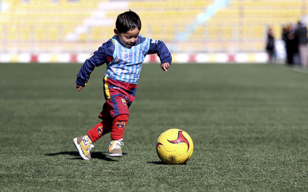 FILE - In this Feb. 2, 2016, file photo, Murtaza Ahmadi, a five-year-old Afghan Lionel Messi fan plays soccer, at the Afghan Football F...