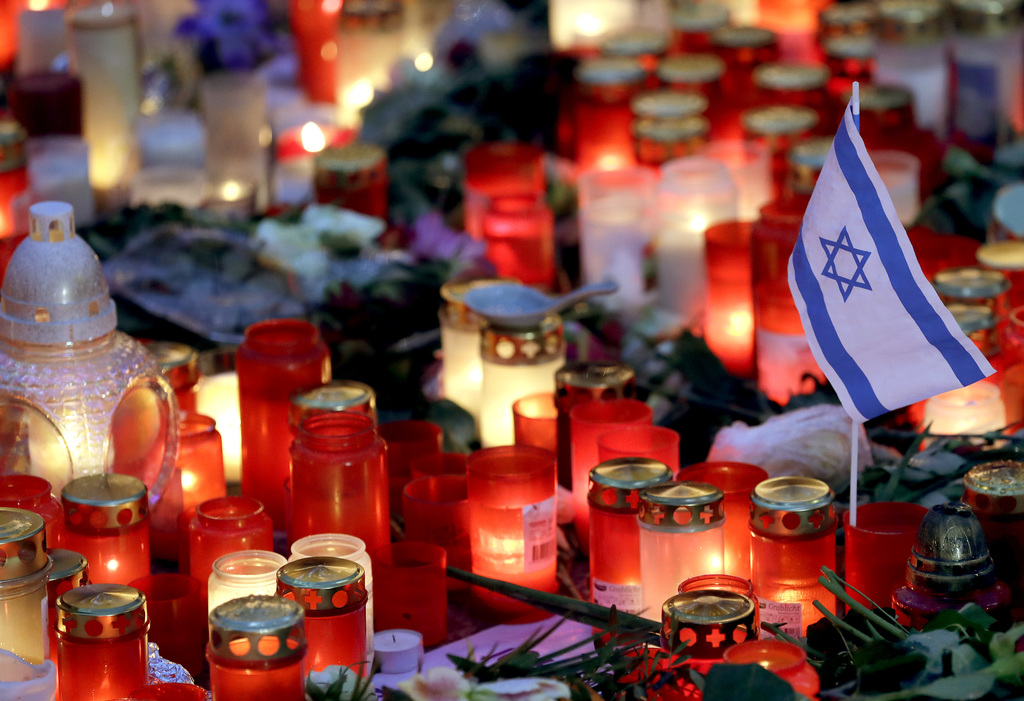 A small flag of Israel is pictured between candles and flowers after the reopening of the Christmas market at the Kaiser Wilhelm Memori...