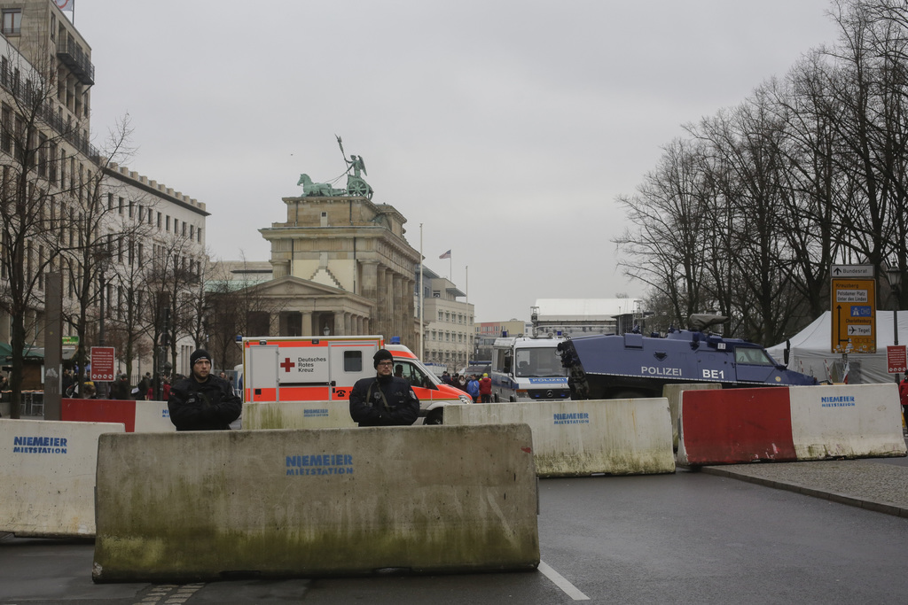 Armed police officers stand behind concrete blocks for protection near the Brandenburg Gate, background, in Berlin, Friday, Dec. 23, 20...