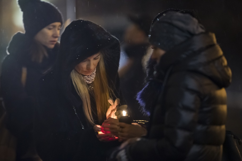 Women try to light a candle to place with flowers in front of the Alexandrov Ensemble building in Moscow, Russia, Monday, Dec. 26, 2016...
