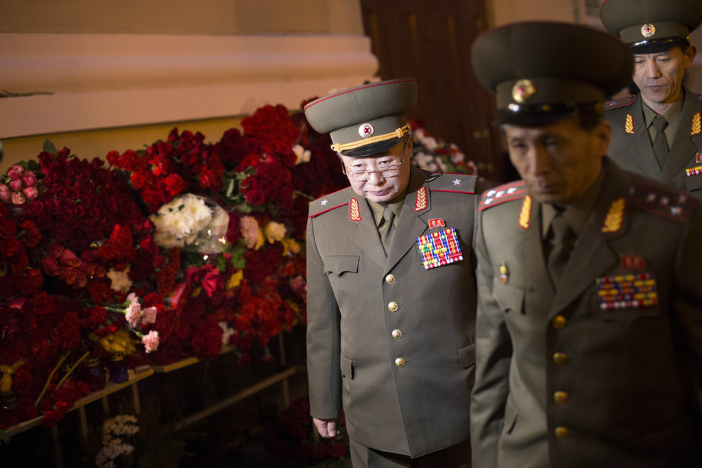North Korean officers place flowers in front of the Alexandrov Ensemble building in Moscow, Russia, Monday, Dec. 26, 2016, after a plan...