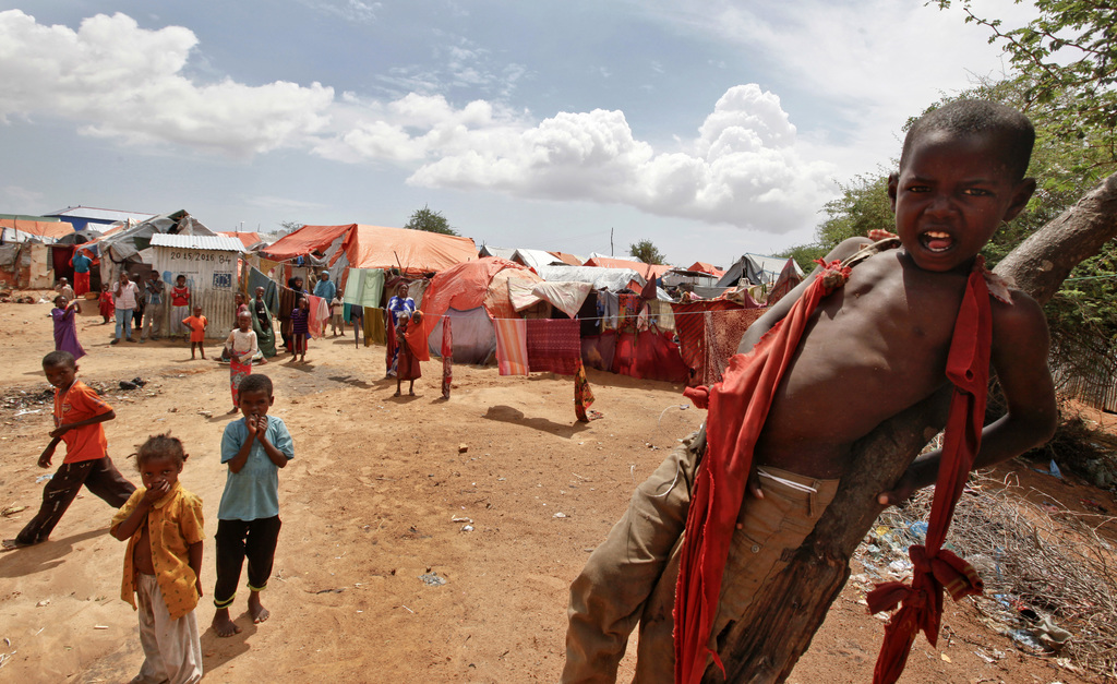 In this photo taken Wednesday, Nov. 16, 2016, Somali children who were repatriated to Somalia from Kenya's Dadaab camp, play in front o...