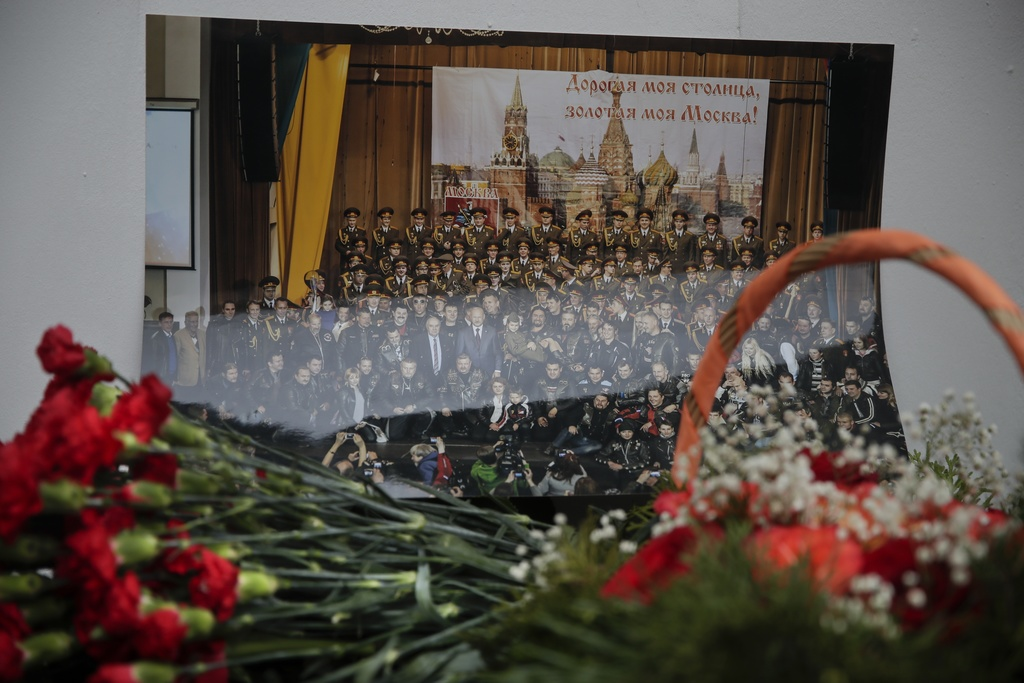 Flowers lay in front of a photo of a well-known military choir lays flowers at the military choir's building in Moscow, Russia, Sunday,...