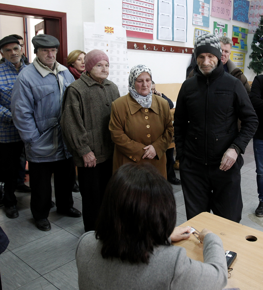 People wait to vote at a polling station in Tearce, northwestern Macedonia, Sunday, Dec. 25, 2016. Authorities in Macedonia have ordere...
