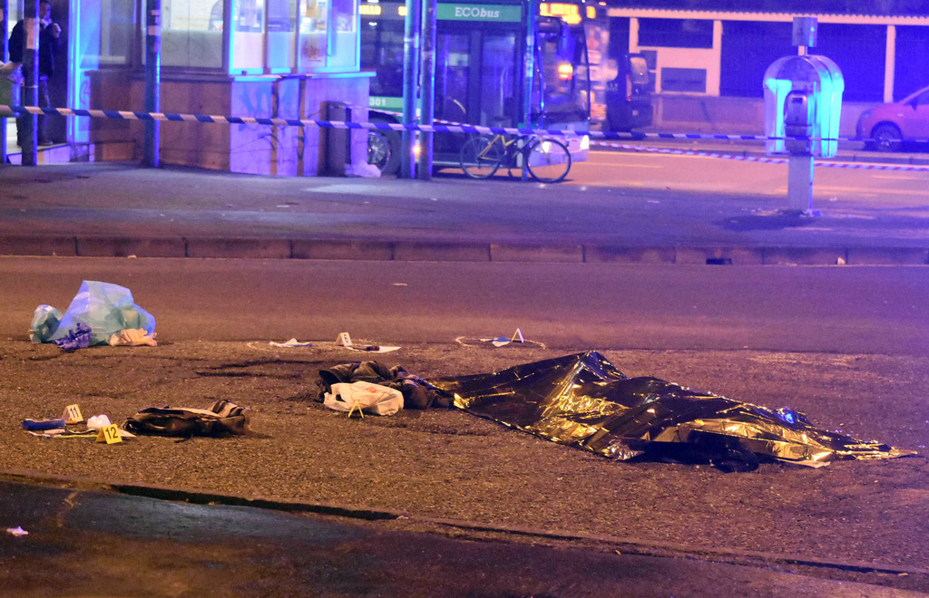 A thermical blanket covers a body moments after a shootout between police and a man near a train station in Milan's Sesto San Giovanni ...