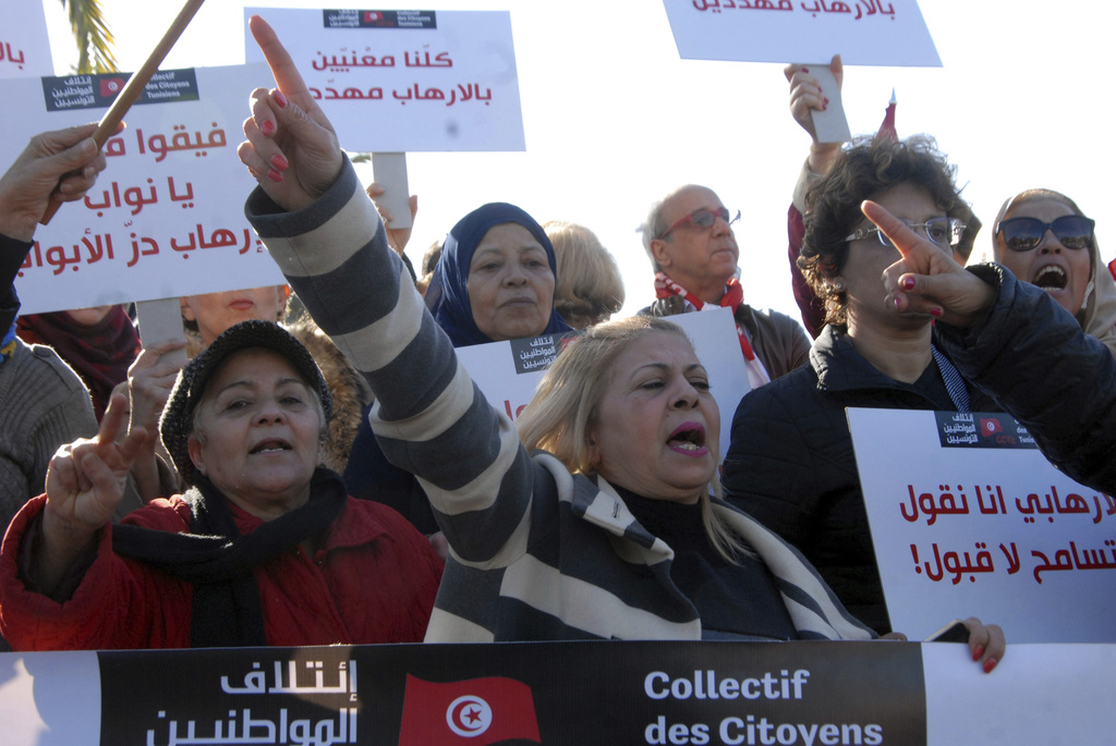People demonstrate outside the Tunisian parliament, in Tunis, Saturday, Dec. 24, 2016. About 200 people have protested in the Tunisian ...