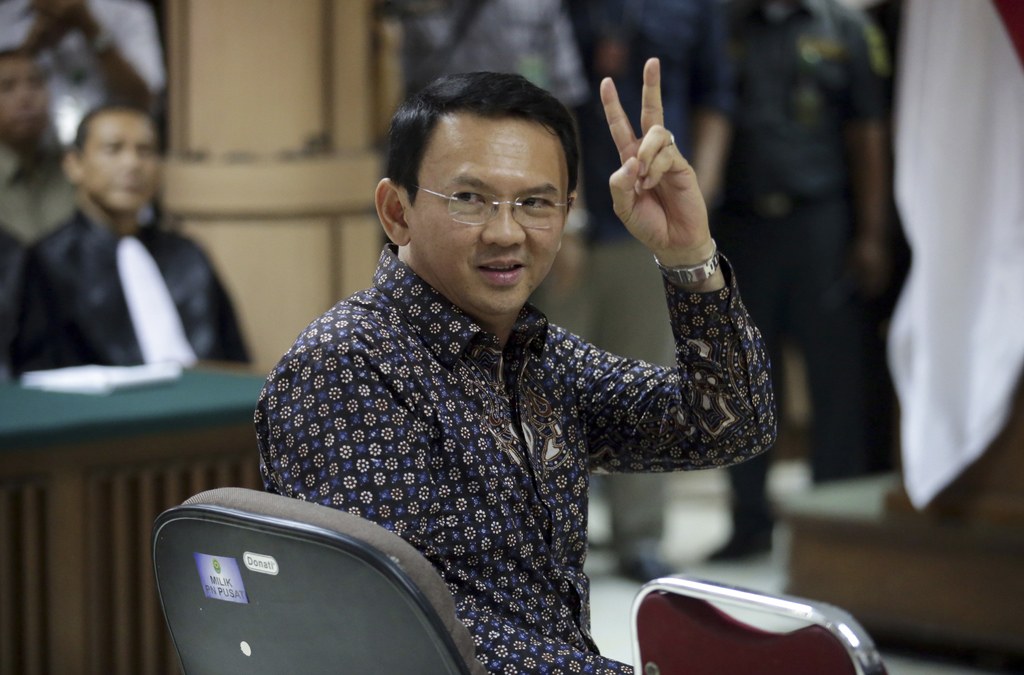 """Jakarta Governor Basuki """"Ahok"""" Tjahaja Purnama gestures to visitors inside a courtroom during his trial at North Jakarta District Court..."""