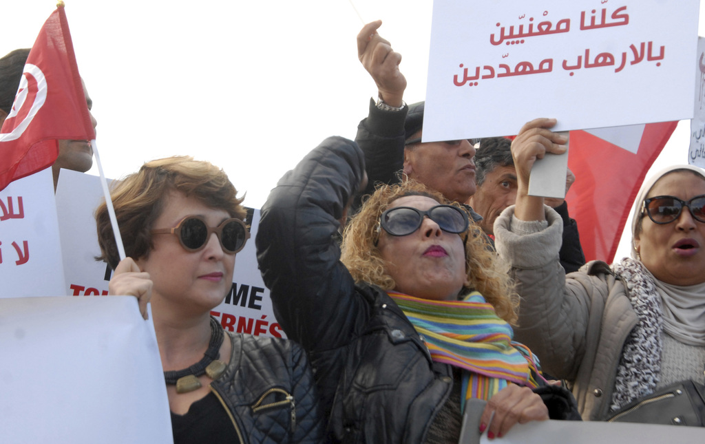 Women demonstrate outside the Tunisian parliament, in Tunis, Saturday, Dec. 24, 2016. About 200 people have protested in the Tunisian c...