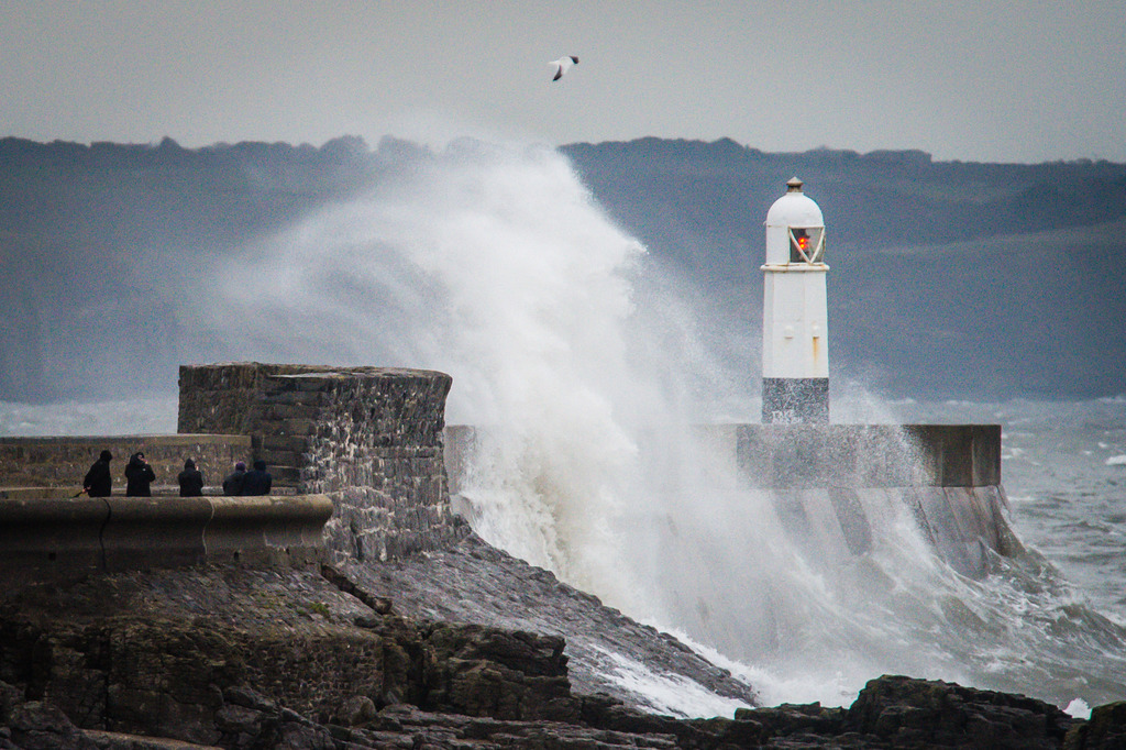 People watch waves crash over the harbour wall at Porthcawl, South Wales, Friday Dec, 23, 2016, as Britain and Ireland are braced for t...