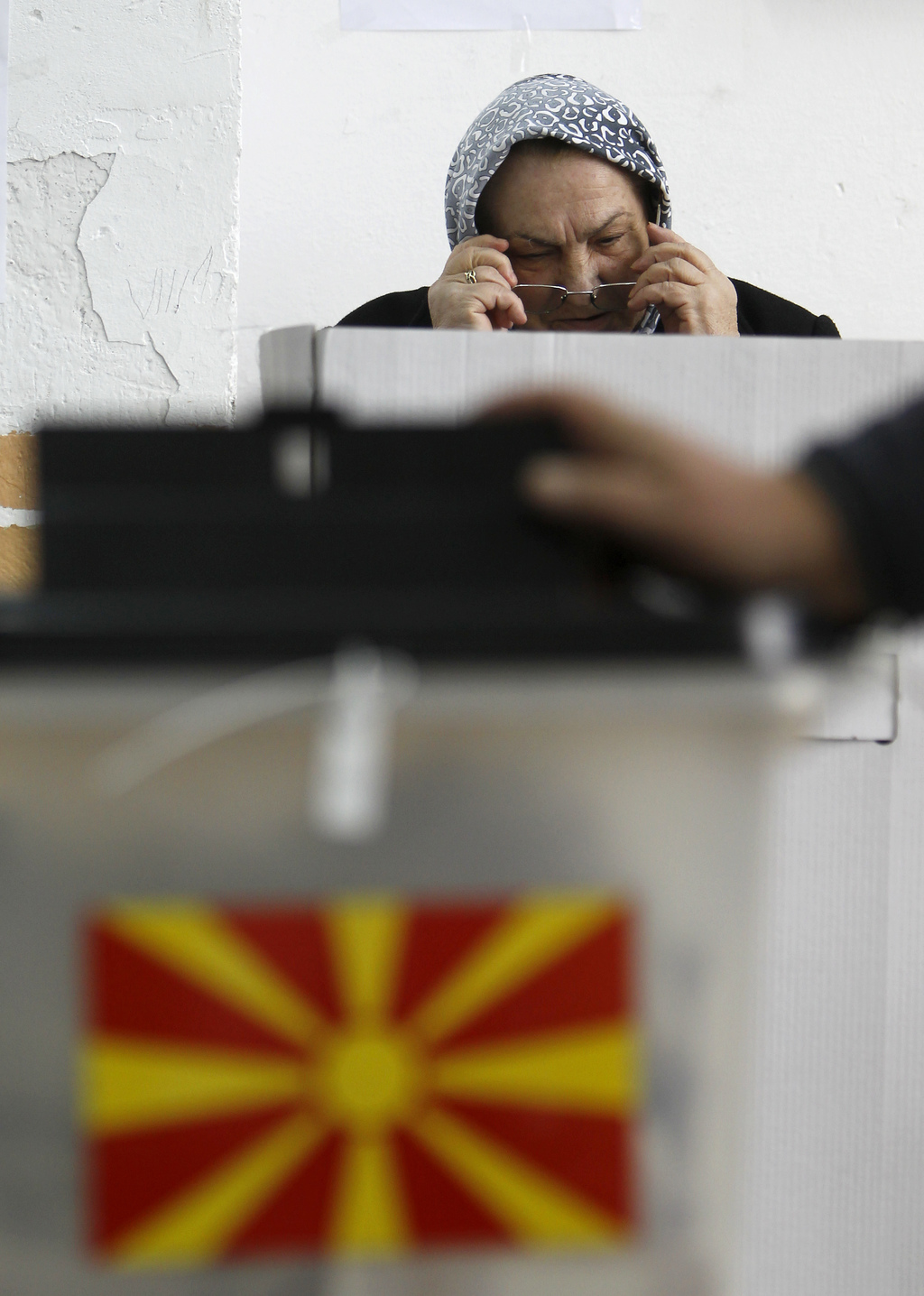 A woman puts on her glasses before voting at a polling station in village of Tearce, in northwestern Macedonia, on Sunday, Dec. 25, 201...