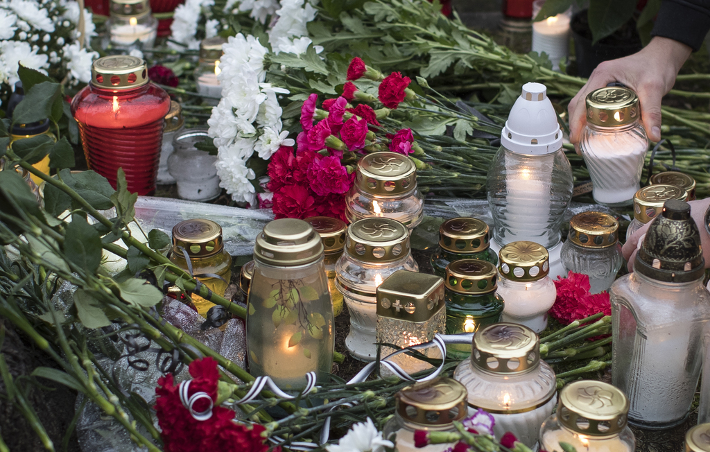 Flowers and candles are placed in memory of victims of the crashed plane in front of the Russia's Embassy in Vilnius, Lithunia, Monday,...