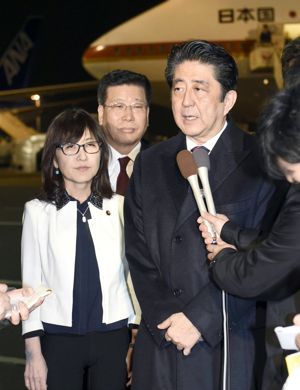 Japanese Prime Minister Shinzo Abe, right, accompanied by Defense Minister Tomomi Inada, left, speaks to the media before his departure...