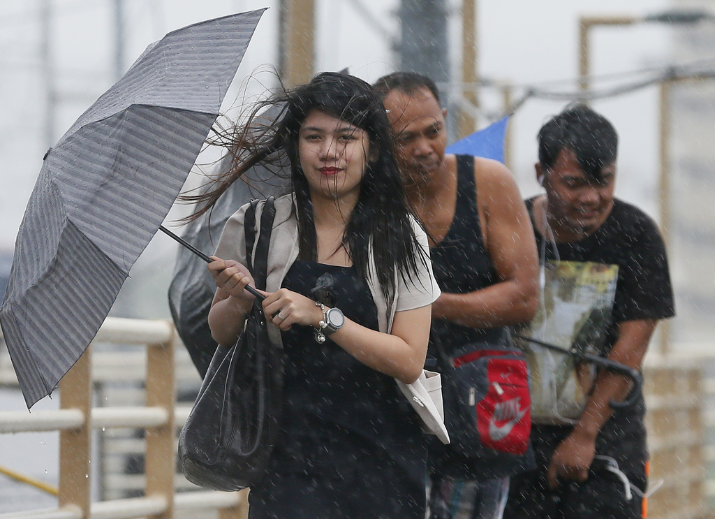People brave the rain and wind brought about by typhoon Nock-Ten, a day after Christmas Monday, Dec. 26, 2016 at suburban Paranaque cit...