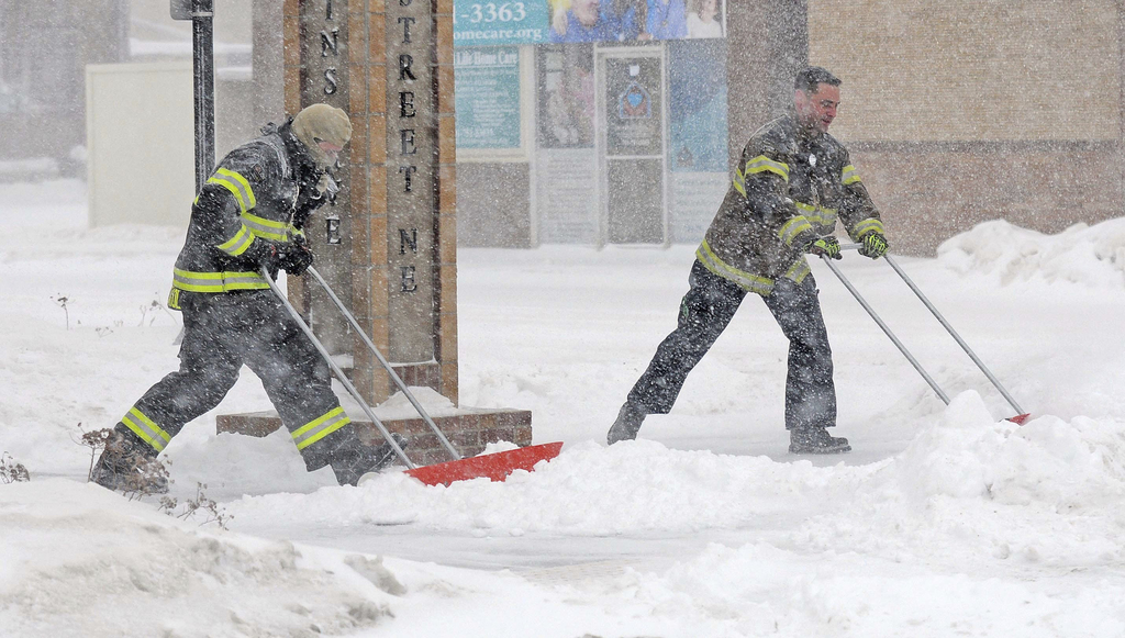 Mandan firefighters Shane Weltikol, left, and Chad Nicklos clear accumulating snow from outside the firehouse in downtown Mandan, N.D.,...