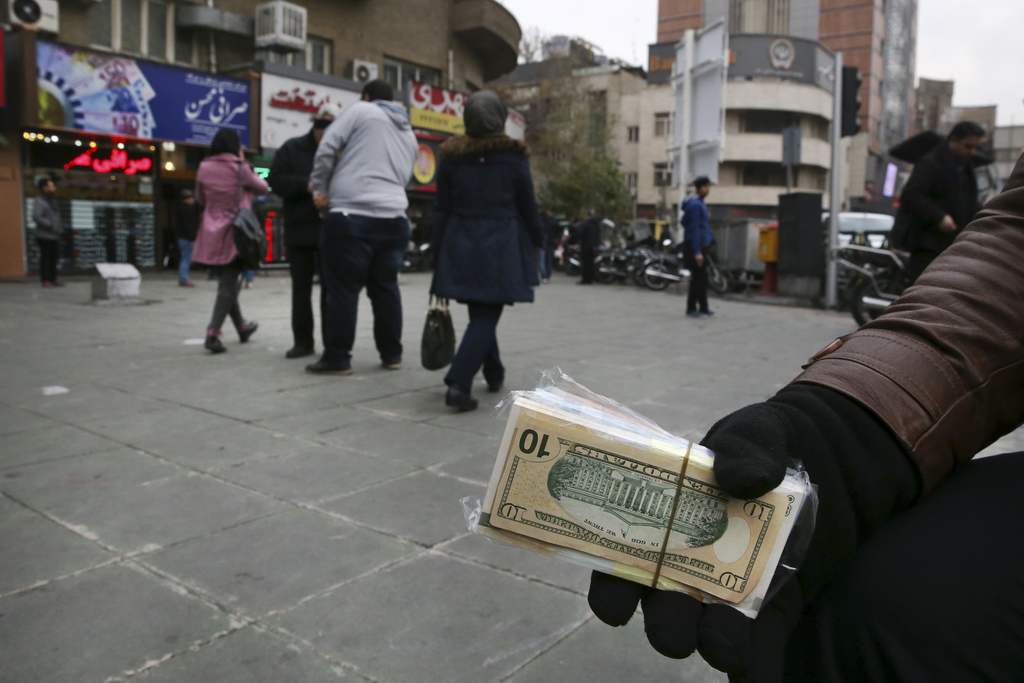 In this picture taken on Monday, Dec. 26, 2016, a street money exchanger holds Iranian and U.S. banknotes in downtown Tehran, Iran. Ira...