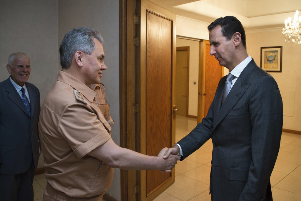 FILE -- In this June 18, 2016 file photo, Syrian President Bashar Assad, right, shakes hands with Russian Defense Minister Sergei Shoig...