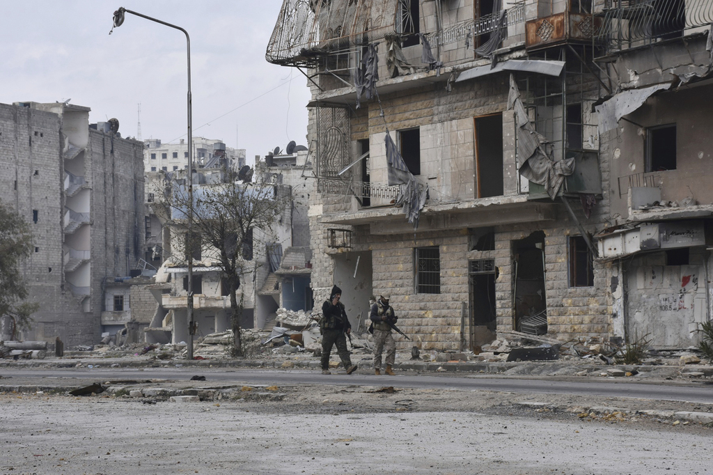 This photo released by the Syrian official news agency SANA shows Syrian army soldiers marching through the streets in the Ansari neigh...