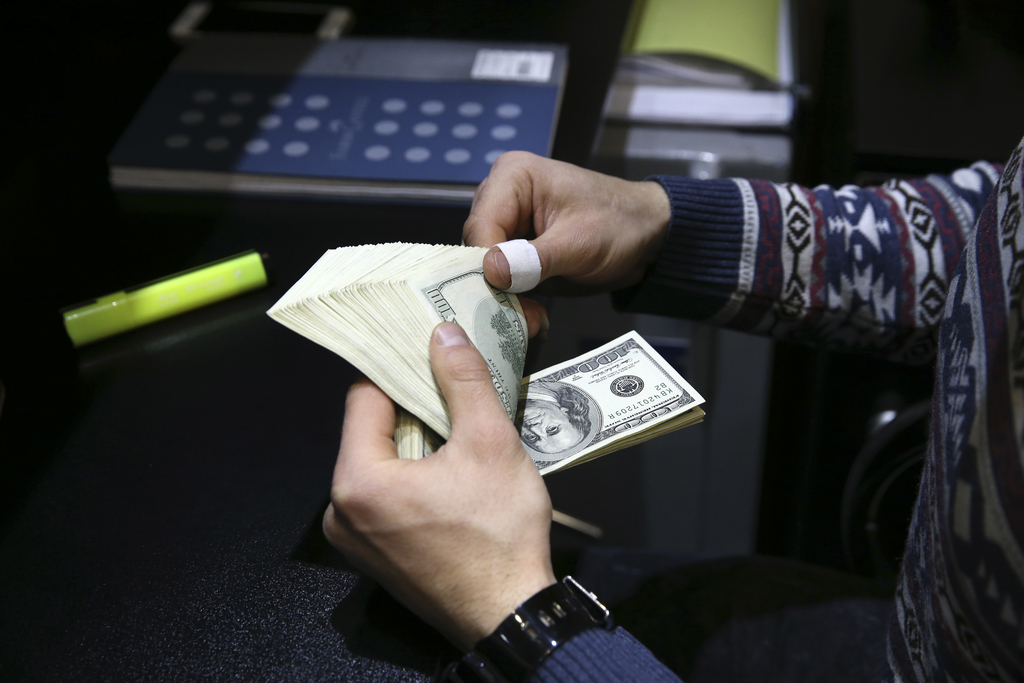 In this picture taken on Monday, Dec. 26, 2016, a currency exchange bureau owner counts U.S. dollars in downtown Tehran, Iran. Iran's c...