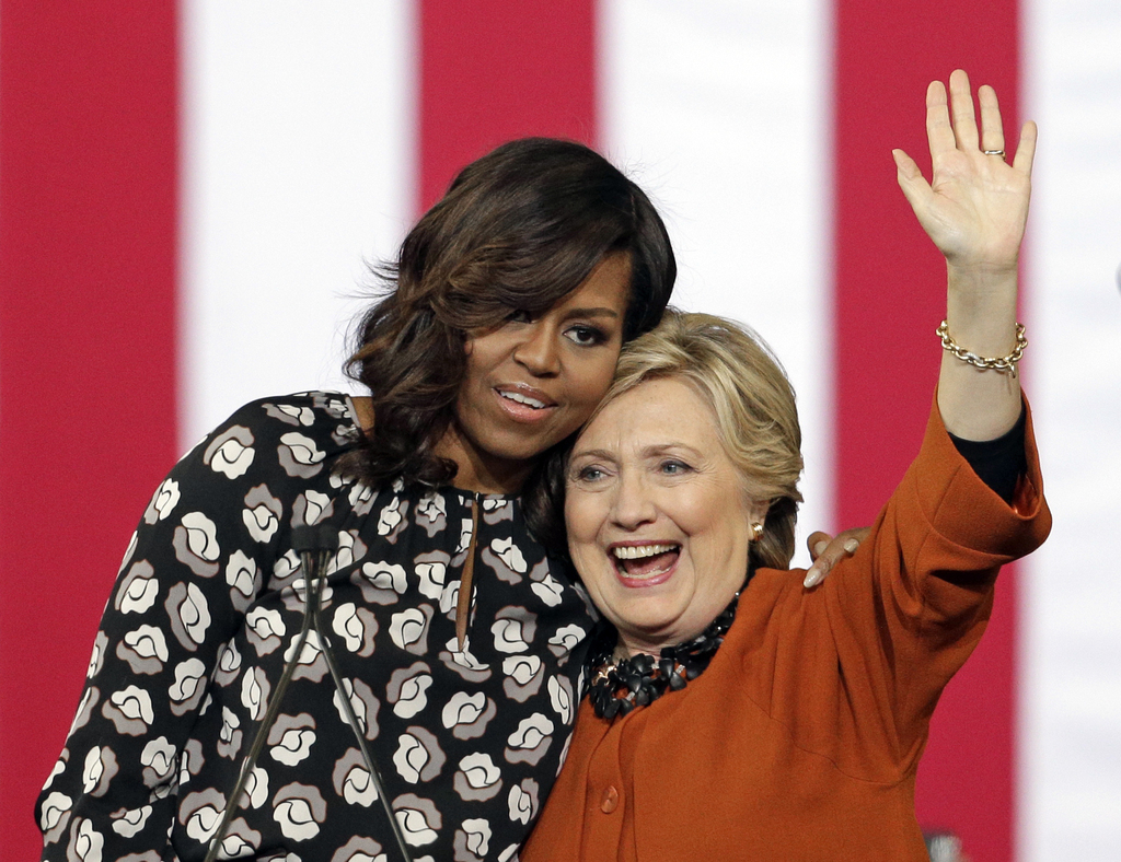 FILE - In this Oct. 27, 2016, file photo, Democratic presidential candidate Hillary Clinton is hugged by first lady Michelle Obama duri...