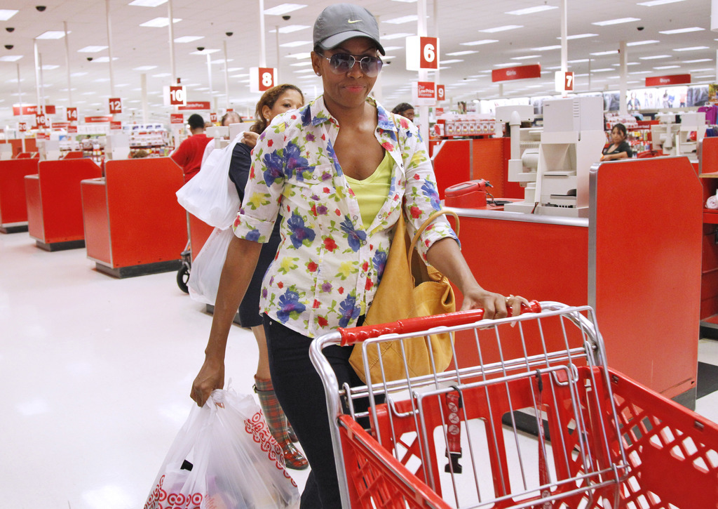 FILE - In this Sept. 29, 2011, file photo, first lady Michelle Obama, wearing a hat and sunglasses, stands in line at a Target departme...