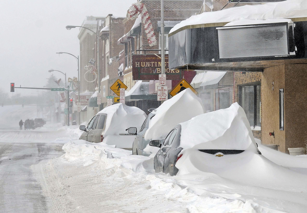 Vehicles piled high with snow in Mandan, N.D., Monday, Dec. 26, 2016. The combination of freezing rain, snow and high winds that forced...