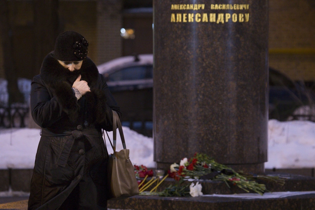 A woman mourns standing in front of monument to Alexander Alexandrov, founder of the Alexandrov Ensemble, near the Alexandrov Ensemble ...