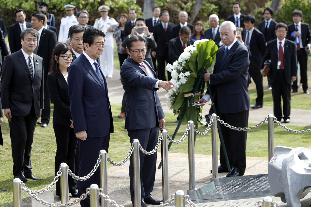 Sal Miwa, of the Japan-America Society of Hawaii, center, shows Japanese Prime Minister Shinzo Abe the Ehime Maru Memorial, Monday, Dec...