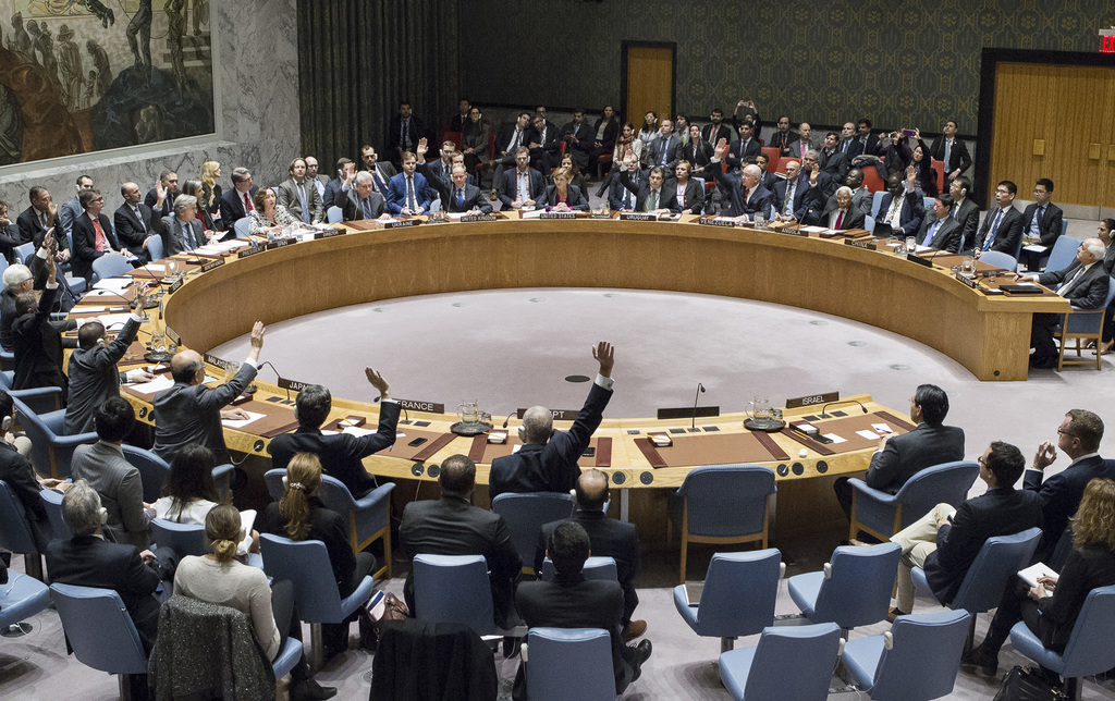 In this photo provided by the United Nations, members of the United Nations Security council vote at the United Nations headquarters on...
