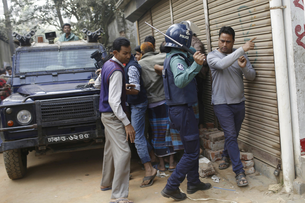 A policeman uses a baton to control the crowd near the area where suspected militants are hiding in Dhaka, Bangladesh, Saturday, Dec. 2...