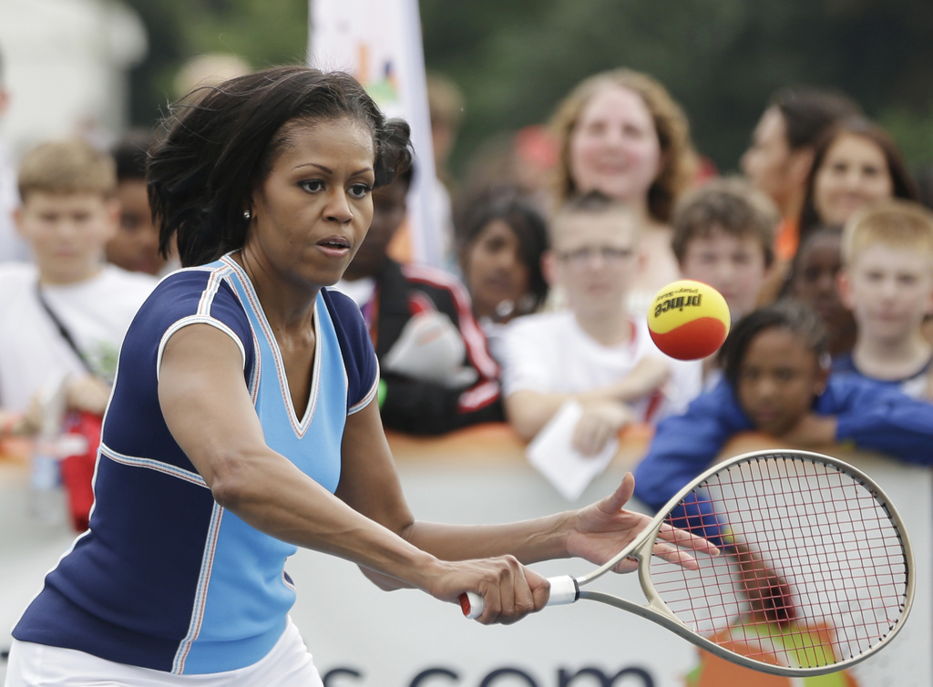 FILE - In this July 27, 2012, file photo, first lady Michelle Obama plays tennis with schoolchildren during a 'Let's Move!' event for a...