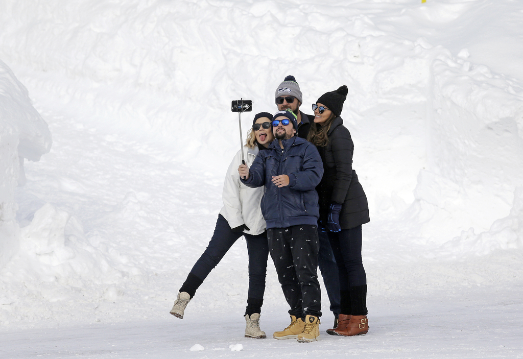 In this photo taken Friday, Dec. 16, 2016, a group of people huddle together to take a selfie photo on a cell phone at the Paradise are...