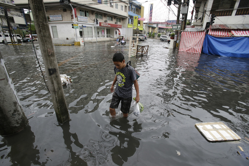A man wades along a flooded street caused by rains from Typhoon Nock-Ten in Quezon city, north of Manila, Philippines on Monday, Dec. 2...