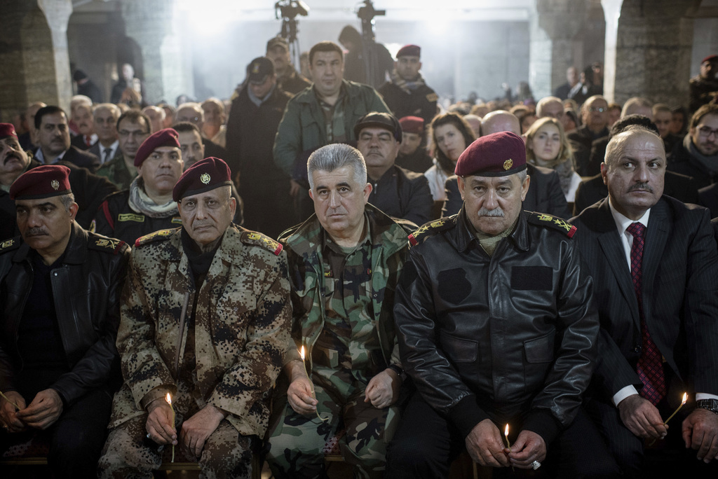 Iraqi Army and Peshmerga commanders attend Christmas Eve's Mass in the Assyrian Orthodox church of Mart Shmoni, in Bartella, Iraq, Satu...