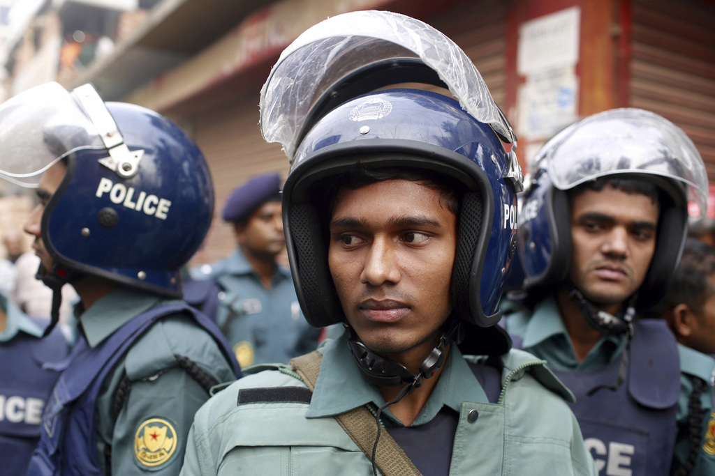 Policemen stand guard after cordoning off the building where suspected militants are hiding in Dhaka, Bangladesh, Saturday, Dec. 24, 20...