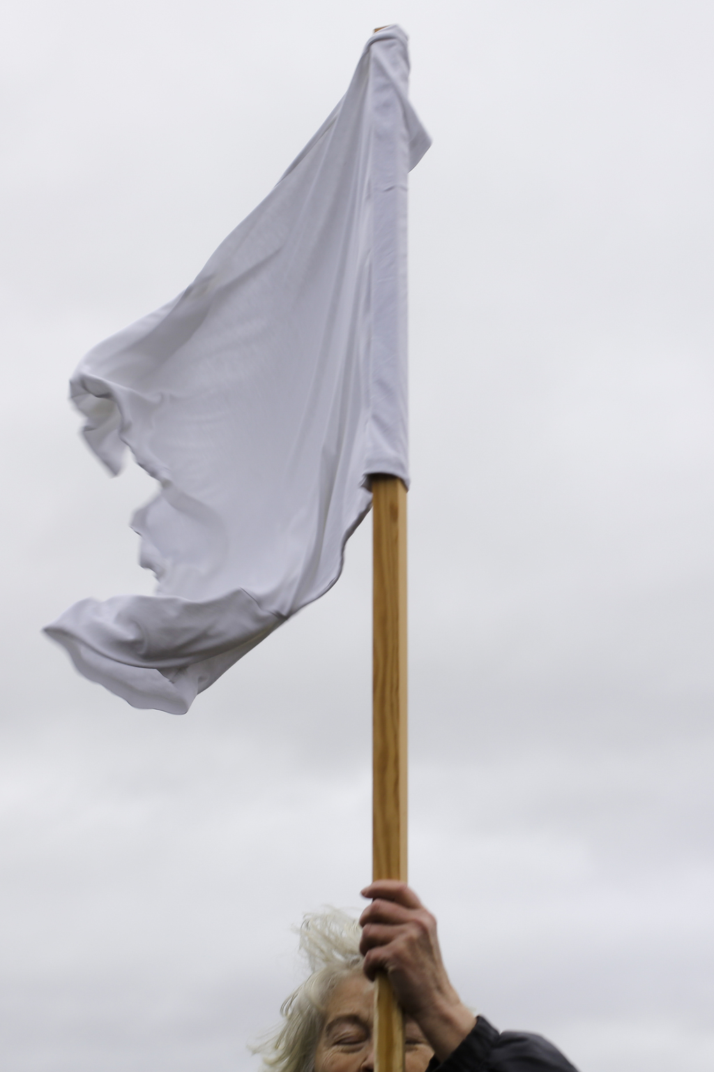 A demonstrator holds a white flag as she attends the Civil March for Aleppo at the air field of the former airport Tempelhof in Berlin,...