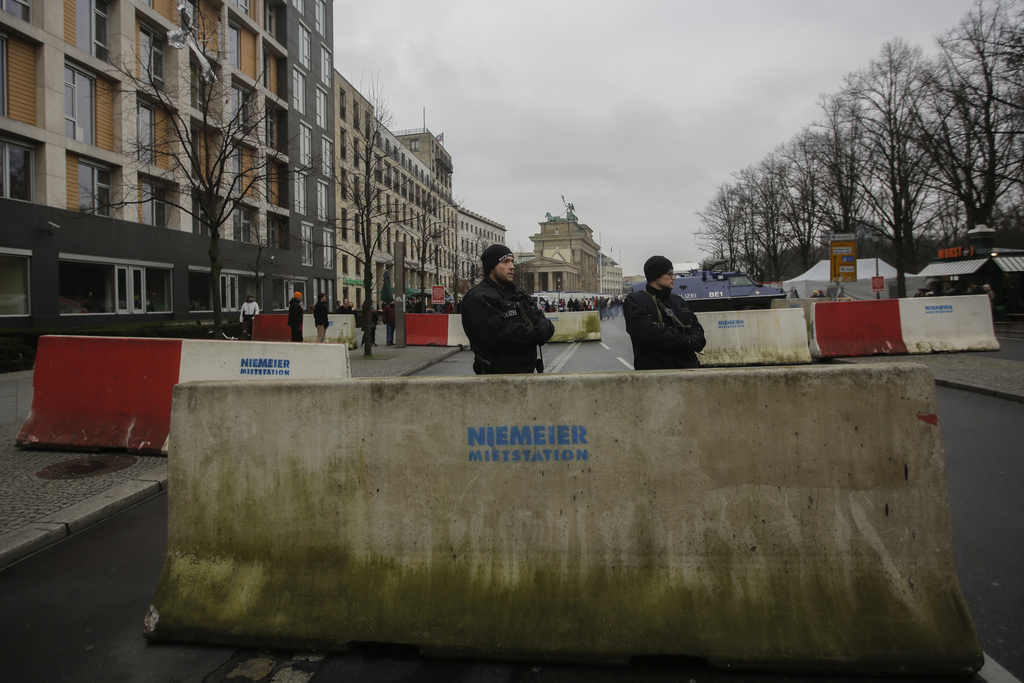 Armed police officers stand behind concrete blocks for protection near the Brandenburg Gate in Berlin, Friday, Dec. 23, 2016, after Ani...